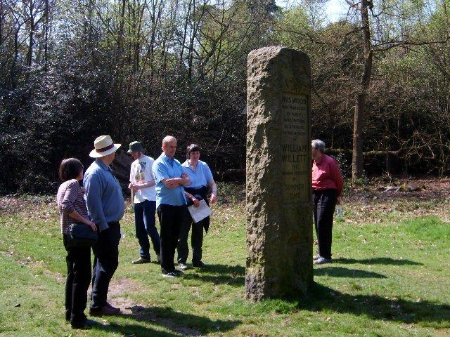 The walkers check the time using the William Willett memorial sundial