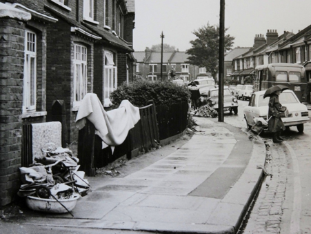 """Walking down the street, I saw women hanging out carpets on their front garden washing lines, to disinfect in the sun. The pictures show abandoned household goods in the street, remarkably few, because many people had so little."" (Janet Roberts)"