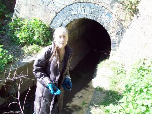 Pamela with pebbles from River Quaggy, Chinbrook Meadows, where river enters the tunnel to go under the railway line flowing towards Lewisham